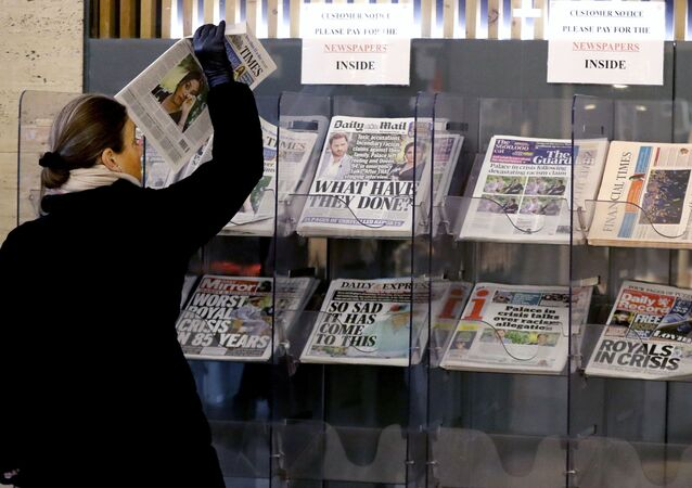 A customer takes a copy of a newspaper headlining Prince Harry and Meghan's explosive TV interview at a newspaper stand outside a shop in London, Tuesday, March 9, 2021