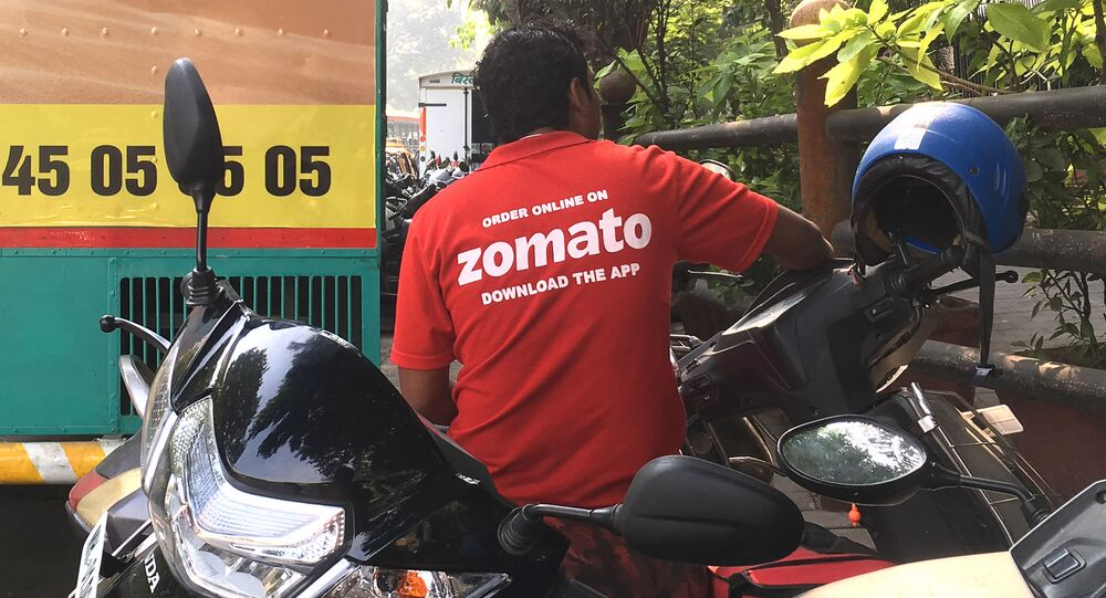 In this photo taken on December 24, 2018, an Indian delivery man working with the food delivery app Zomato sits on his bike in a business district in Mumbai.