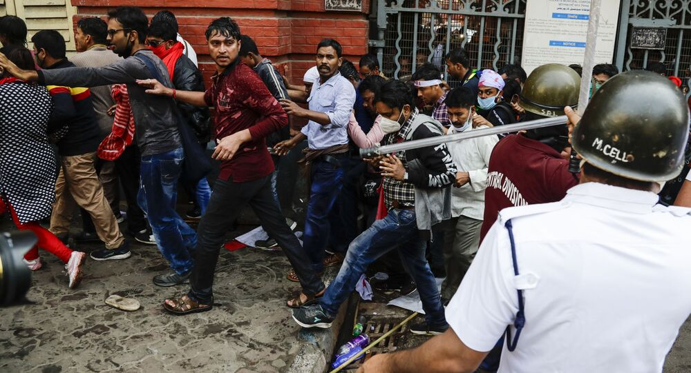 Police chase student activists of the Communist Party of India during a rally against the West Bengal government, as they demand better education and employment opportunities in Kolkata, India, Thursday, Feb. 11, 2021