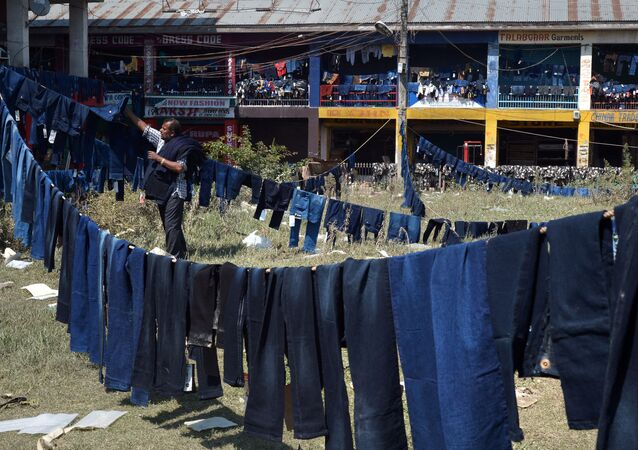 A Kashimri worker of a ready-made garment shop hangs flood-damaged stock to dry in a park outside the shop in Srinagar on September 18, 2014
