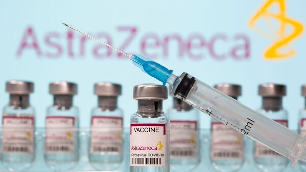 Vials labelled AstraZeneca COVID-19 Coronavirus Vaccine and a syringe are seen in front of a displayed AstraZeneca logo in this illustration taken 10 March 2021. REUTERS/Dado Ruvic/Illustration - Sputnik International