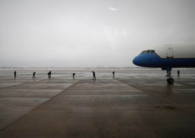 Air Force One crew members scan the tarmac following a previous day ice storm, ahead of U.S. President Joe Biden's trip to Michigan, at Joint Base Andrews in Maryland, U.S., February 19, 2021.