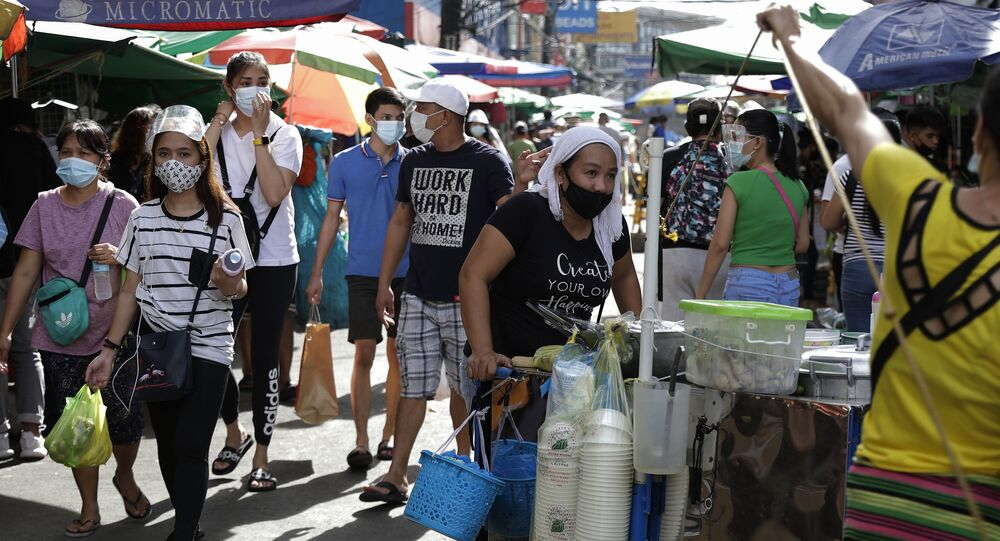 People wear face masks to help prevent the spread of coronavirus as they walk along a busy market area in downtown Manila on Wednesday, 6 January 2021.