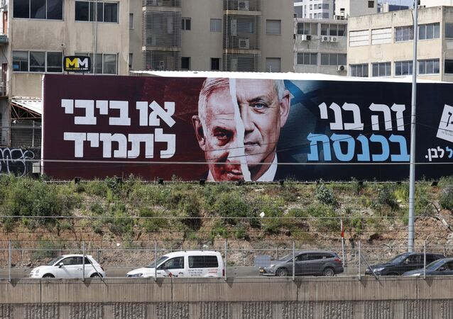 Cars drive past an election campaign billboard for Israel's Blue and White opposition party led by Benny Gantz (R) depicting him and Israeli Prime Minister Benjamin Netanyahu of the Likud party, on a highway in the coastal city of Tel Aviv, on March 12, 2021, ahead of the March 23 general election. The writing in Hebrew reads Benny to the Knesset or Bibi for ever.