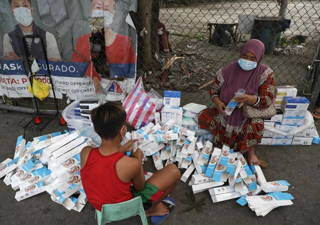 A woman and a boy wearing face masks to prevent the spread of the coronavirus arrange boxes of face shields in Manila, Philippines, Friday, March 12, 2021.