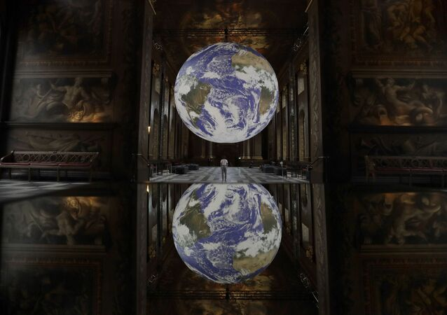 Reflected in a mirrored table Luke Jerram's illuminated 3D installation entitled Gaia, displayed with surround sound from award winning composer Dan Jones, as part of the 2020 Greenwich and Docklands International Festival, at the Royal Naval College in London, 28 August 2020