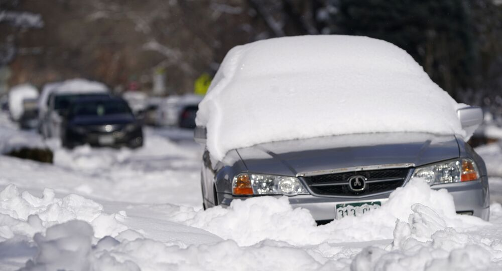 A sedan is buried after more than a foot of snow left by a late winter storm that swept over the region Thursday, Feb. 25, 2021, in Denver. The storm moved away from Colorado's Front Range communities and on to the eastern plains overnight.