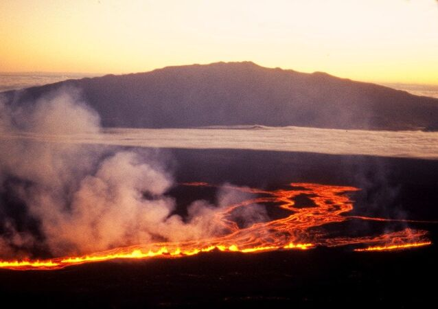 The sun rises beyond Mauna Kea as lava flows down the side of Mauna Loa on the morning of July 6th, 1975