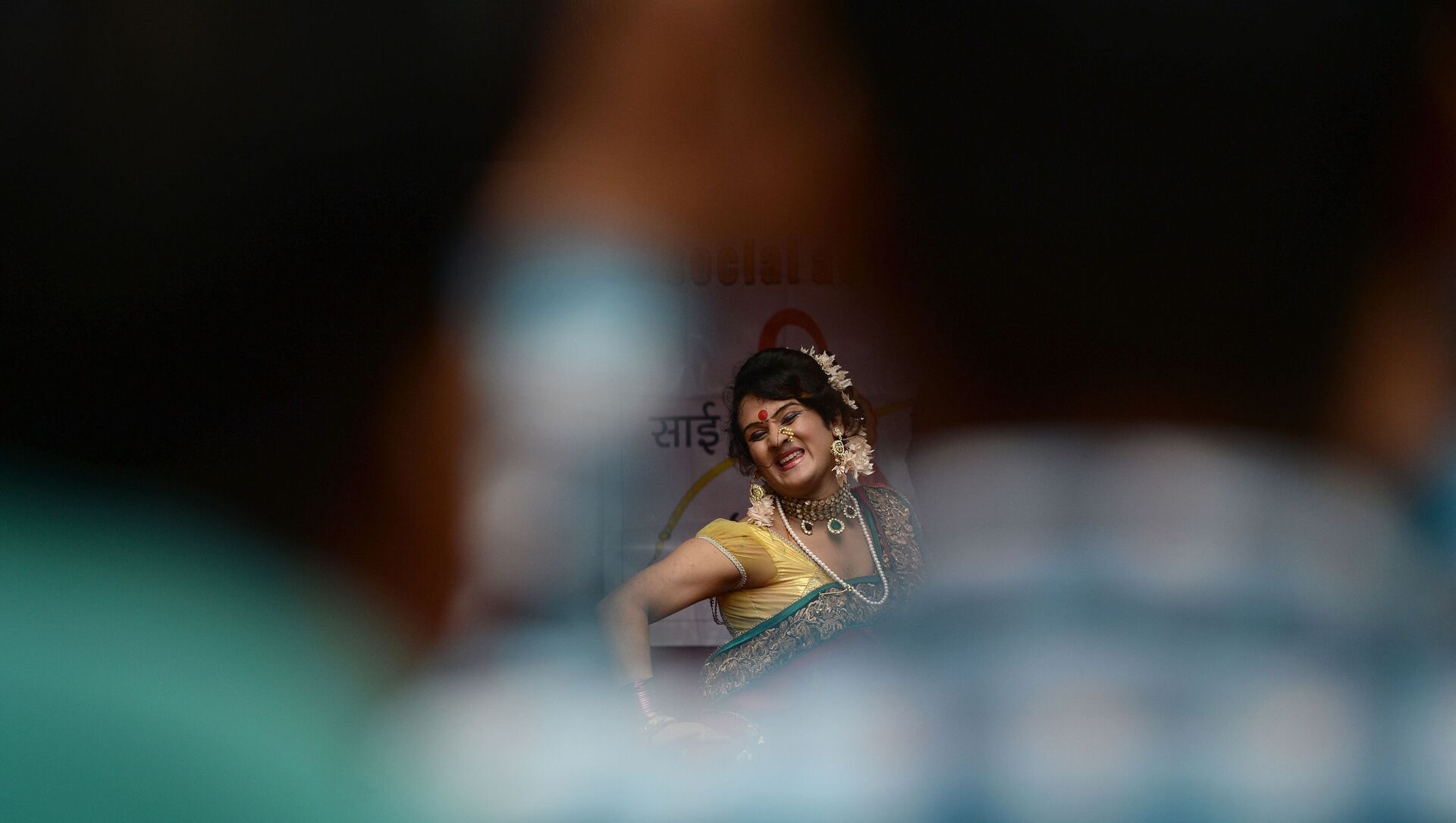 A  traditional Lavani folk dancer is seen through a gap among the audience during a performance for sex workers in the red light district of Kamathipura in Mumbai on 28 August 2015, ahead of the Hindu festival 'Raksha Bandhan' - Sputnik International, 1920, 15.03.2021