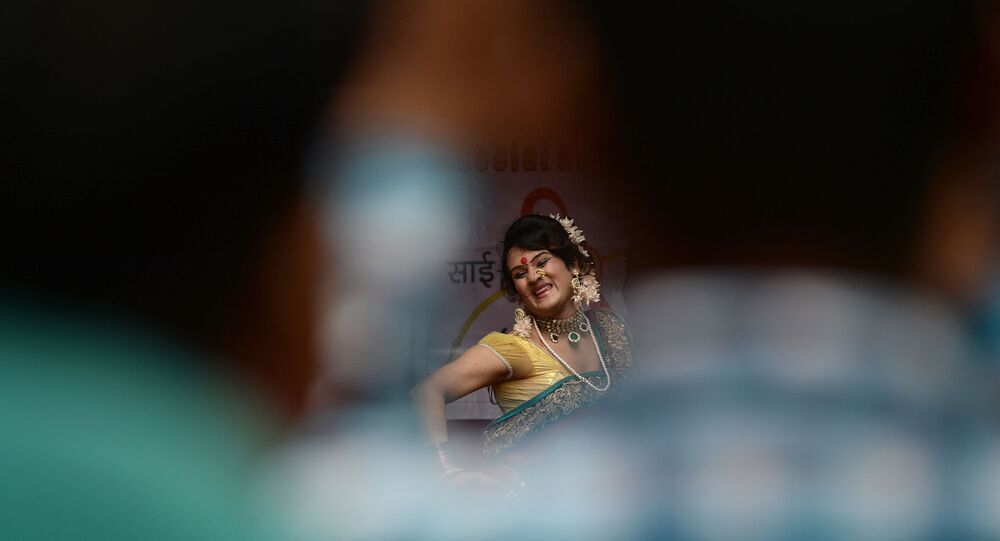 A  traditional Lavani folk dancer is seen through a gap among the audience during a performance for sex workers in the red light district of Kamathipura in Mumbai on 28 August 2015, ahead of the Hindu festival 'Raksha Bandhan'