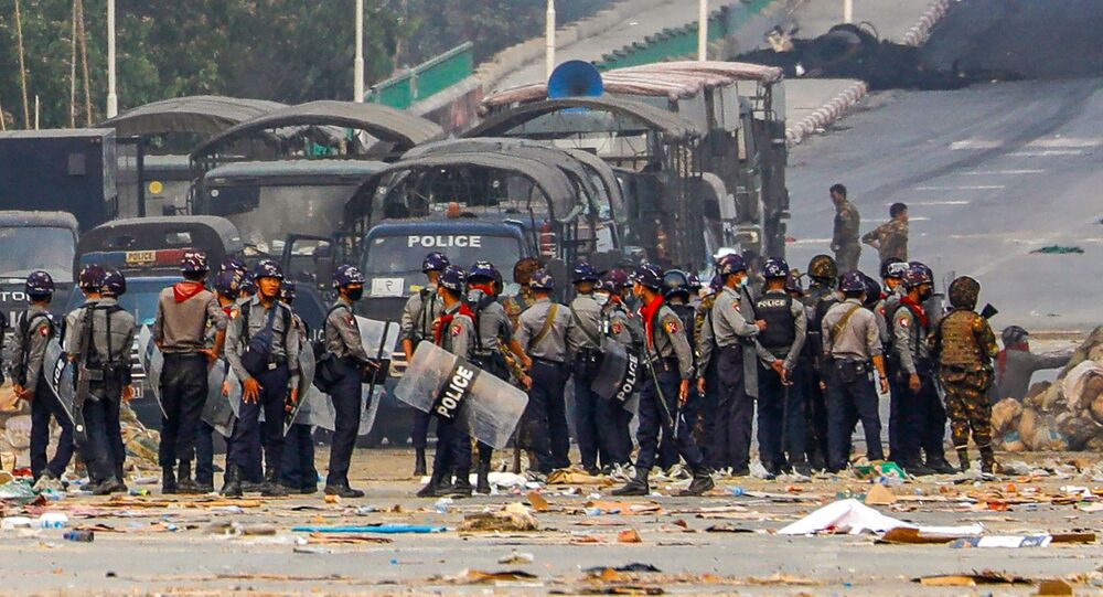 Police stand near makeshift barricades set up by protesters during a crackdown on demonstrations against the military coup in Hlaing Tharyar township in Yangon on March 14, 2021.