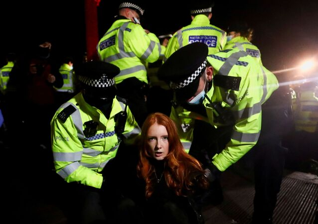 Police detain a woman as people gather at a memorial site in Clapham Common Bandstand, following the kidnap and murder of Sarah Everard, in London, Britain