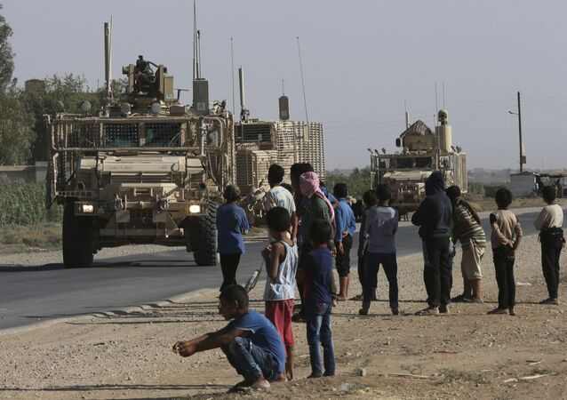 In this 26 July 2017 file photo, Syrian children and youths gather on a street as they look at a US armoured vehicle convoy pass on a road that heads to Raqqa, north-east Syria.