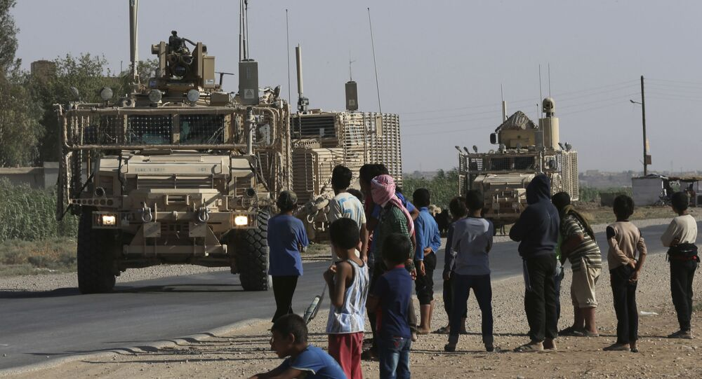 In this July 26, 2017 file photo, Syrian children and youths gather on a street as they look at a U.S. armored vehicle convoy pass on a road that links to Raqqa, northeast Syria.