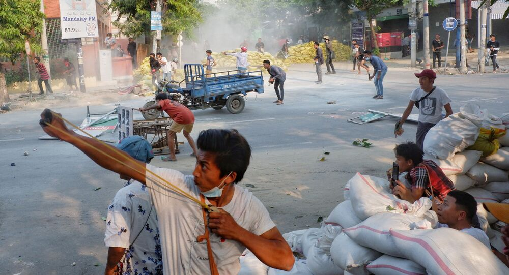 A man uses a slingshot during the security force crack down on anti-coup protesters in Mandalay, Myanmar