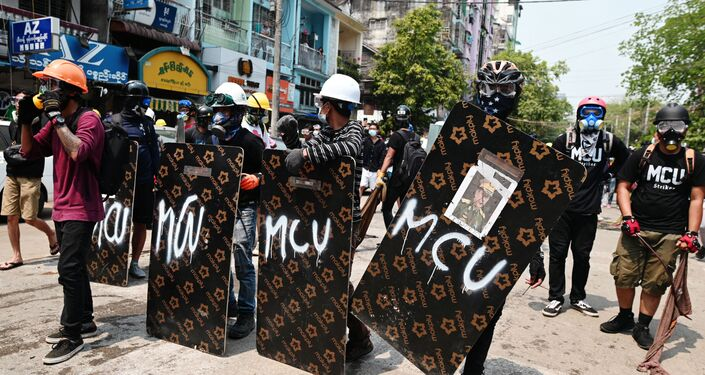 Demonstrators stand behind makeshift shields during an anti-coup protest in Yangon