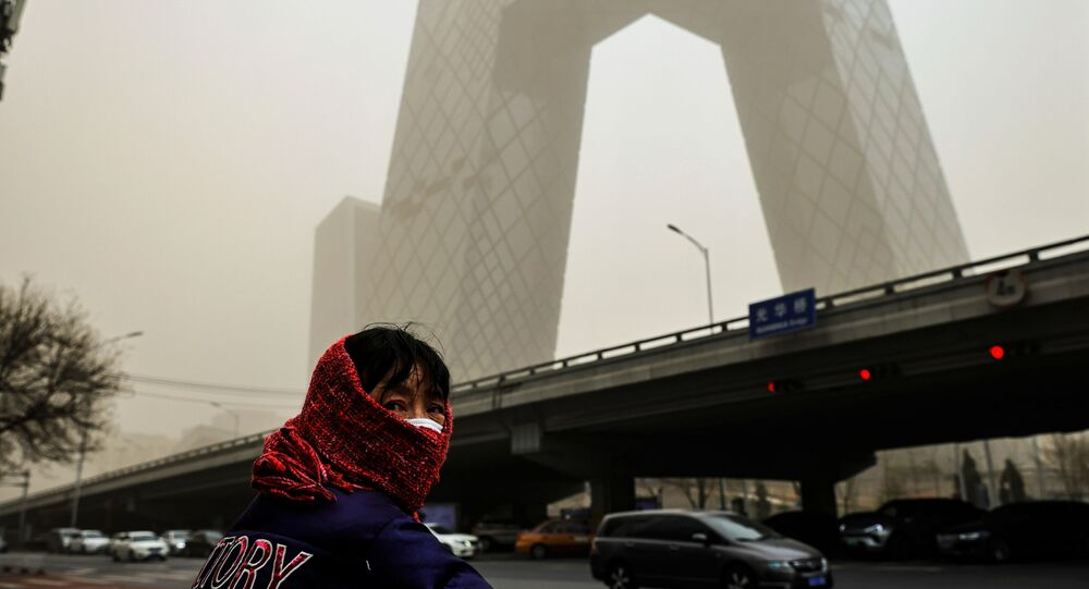 A woman wearing a head covering is seen in front of the headquarters of China's state media broadcaster CCTV that is shrouded in a haze after a sandstorm in the Central Business District of Beijing, China.