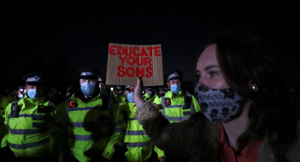 A woman hold a sign in front of police as people gather at a memorial site in Clapham Common Bandstand, following the kidnap and murder of Sarah Everard, in London, Britain March 13, 2021. REUTERS/Hannah McKay