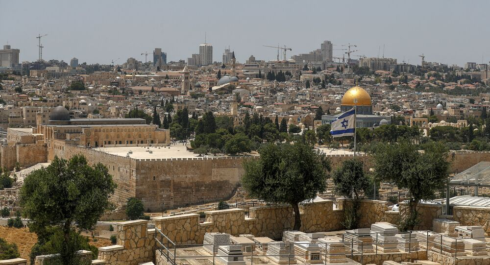 This picture taken on 30 July 2020 from the Mount of the Olives shows an Israeli flag flying in Jerusalem with the Dome of the Rock in the background.