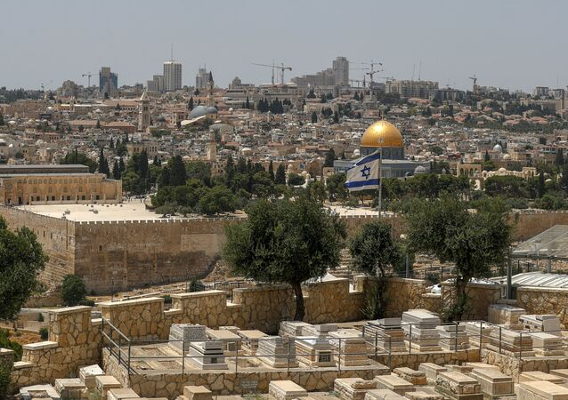 This picture taken on July 30, 2020 from the Mount of the Olives shows a view of an Israeli flag flying in Jerusalem with the Dome of the Rock seen in the background