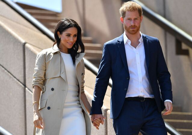 (FILES) In this file photo taken on October 16, 2018 Britain's Prince Harry and his wife Meghan walk down the stairs of Sydney's iconic Opera House to meet people in Sydney