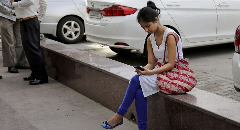 An Indian woman uses her mobile phone  in New Delhi, India, Tuesday, Sept. 22, 2015