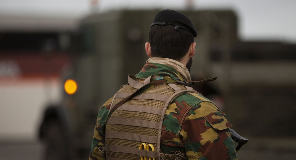 A Belgian solider patrols in a temporary military zone as vehicles arrive from a British naval vessel, taking part in U.S.-led war games, as they are unloaded at the Port of Antwerp in Antwerp, Belgium, Monday Feb. 3, 2020.