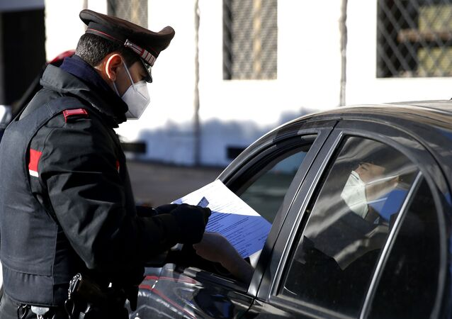 Carabinieri police officers check documents at a road block in Rome, Monday, March 15, 2021.