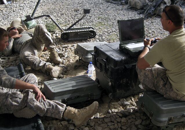 U.S. 101st Airborne Division's 2nd Lt. Corey Wolff, 24, of Chatham, Ohio, right, tests a robot on a resting soldier at Combat Outpost Ashoqeh, Kandahar province, Afghanistan, Sunday, Sept. 12, 2010.