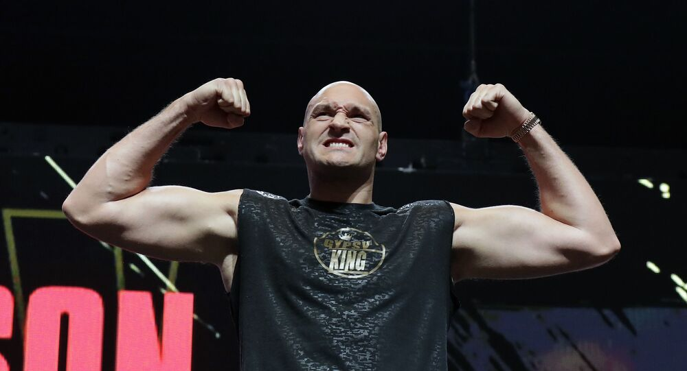 In this Feb. 21, 2020, file photo, Tyson Fury, of England, stands on the scale during a weigh-in for his WBC heavyweight championship boxing match against Deontay Wilder, in Las Vegas.