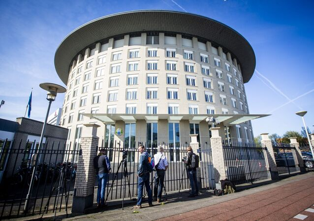 Journalists wait at the entrance of the headquarters of the Organisation for the Prohibition of Chemical Weapons (OPCW) in The Hague, The Netherlands, on April 18, 2018.