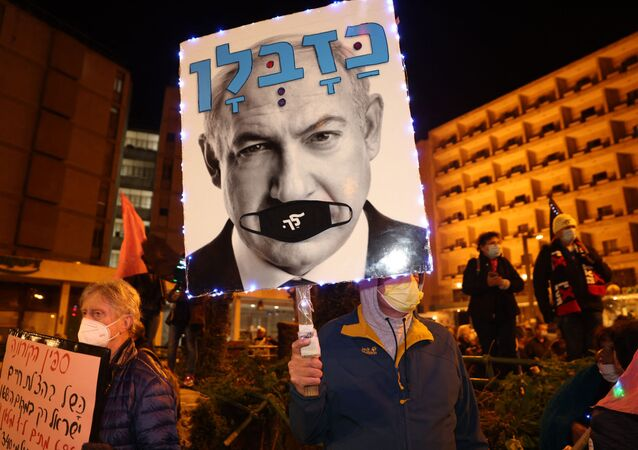 An Israeli protester carries a placard bearing the portraits of Benjamnin Netanyahu during a demonstration against the Prime Minister outside his official residence in Jerusalem on March 13, 2021.