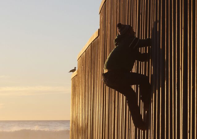 Honduran migrant Jonatan Matamoros Flores, 33, who arrived in October with a migrant caravan, climbs the U.S. border wall to stand atop it before returning to the Mexican side in Tijuana, Mexico, Saturday, Dec. 8, 2018