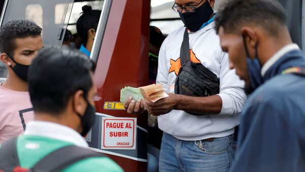 A bus driver's assistant collects fares while holding a wad of Bolivar banknotes at a bus stop outside the Antimano metro station in Caracas, Venezuela, March 9, 2021. Picture taken March 9, 2021. REUTERS/Leonardo Fernandez Viloria  - Sputnik International