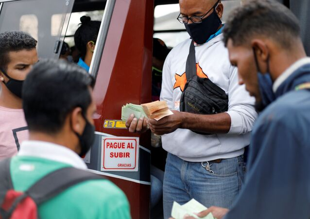 A bus driver's assistant collects fares while holding a wad of Bolivar banknotes at a bus stop outside the Antimano metro station in Caracas, Venezuela, March 9, 2021. Picture taken March 9, 2021. REUTERS/Leonardo Fernandez Viloria