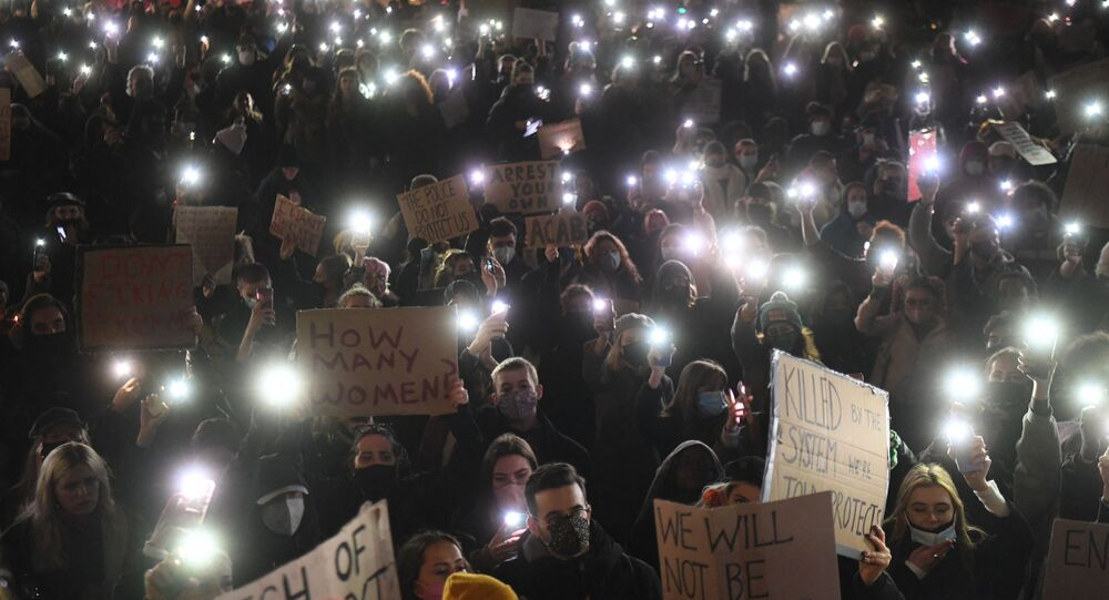 Protesters calling for greater public safety for women after the death of Sarah Everard, against the police handling of a gathering on Clapham Common in Sarah Everard's honour and against a proposed law that would give police more powers to intervene on protests hold up their mobile phones with their torches illuminated in Parliament Square in central London on March 14, 2021. - London's Metropolitan Police on Sunday defended its handling of a high-profile protest calling for greater public safety for women, after male officers were seen scuffling with the crowd and physically restraining female demonstrators. Hundreds defied coronavirus restrictions on Saturday night to gather on Clapham Common park to mark the death of Sarah Everard, who went missing nearby as she walked home earlier this month. A serving police officer with the London force has since been charged with her kidnap and murder.