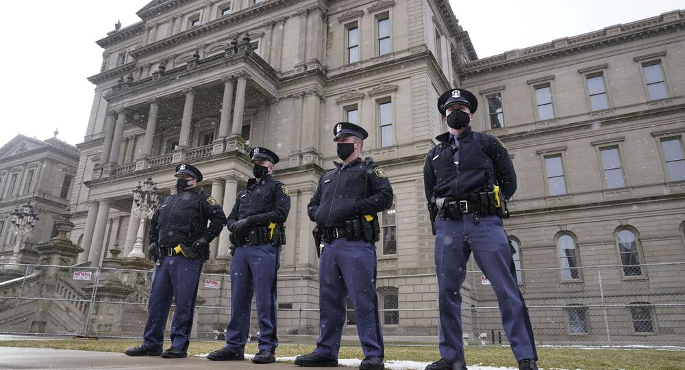 Michigan State Police troopers stand guard outside the state capitol in Lansing, Mich., Sunday, Jan. 17, 2021.