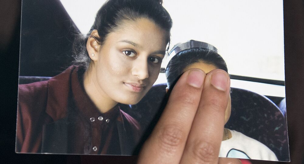 In this file photo, taken on 22 February 2015, Renu, eldest sister of missing British girl Shamima Begum, holds a picture of her sister while being interviewed by the media in central London.
