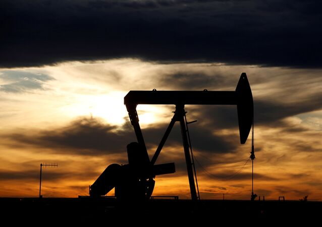 The sun sets behind a crude oil pump jack on a drill pad in the Permian Basin in Loving County, Texas, U.S. November 24, 2019.