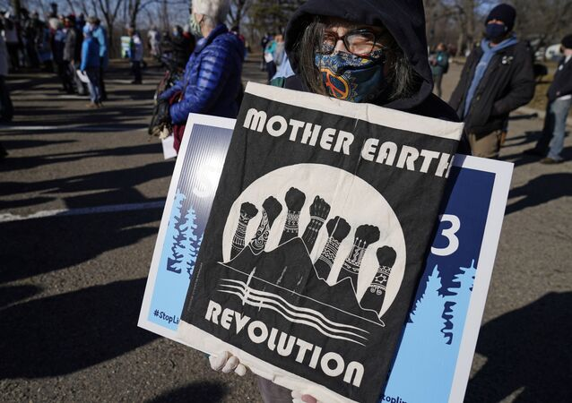Protesters gather along the Mississippi River in St. Paul, Minn., Thursday, March 11, 2021, to call on President Biden to stop the tar sands Line 3 pipeline that Enbridge is currently constructing in northern Minnesota.