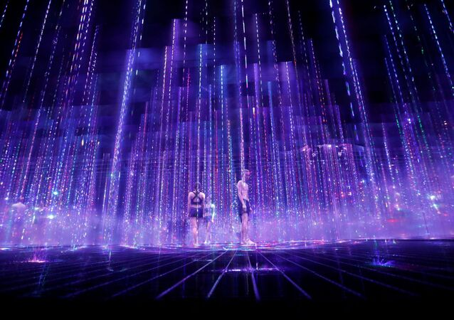 Staff from teamLab wearing swimsuits walk inside a piece of digital artwork combining light, water, and sound during a demonstration of TikTok teamLab Reconnect ahead of its opening to the public this month in Tokyo, Japan, 13 March 2021.