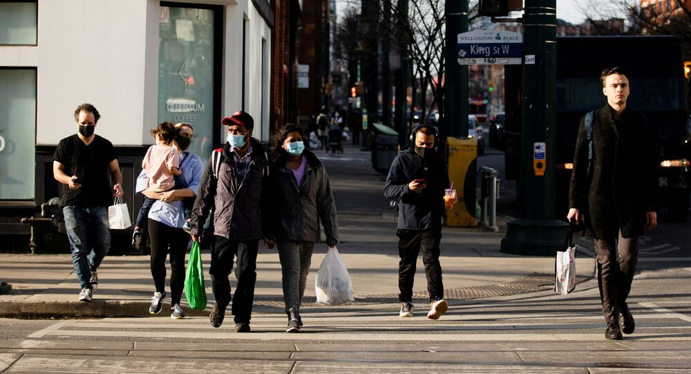 People walk with face masks on the one-year anniversary of the World Health Organization declaring coronavirus disease (COVID-19) a pandemic in Toronto, Ontario, Canada March 11, 2021
