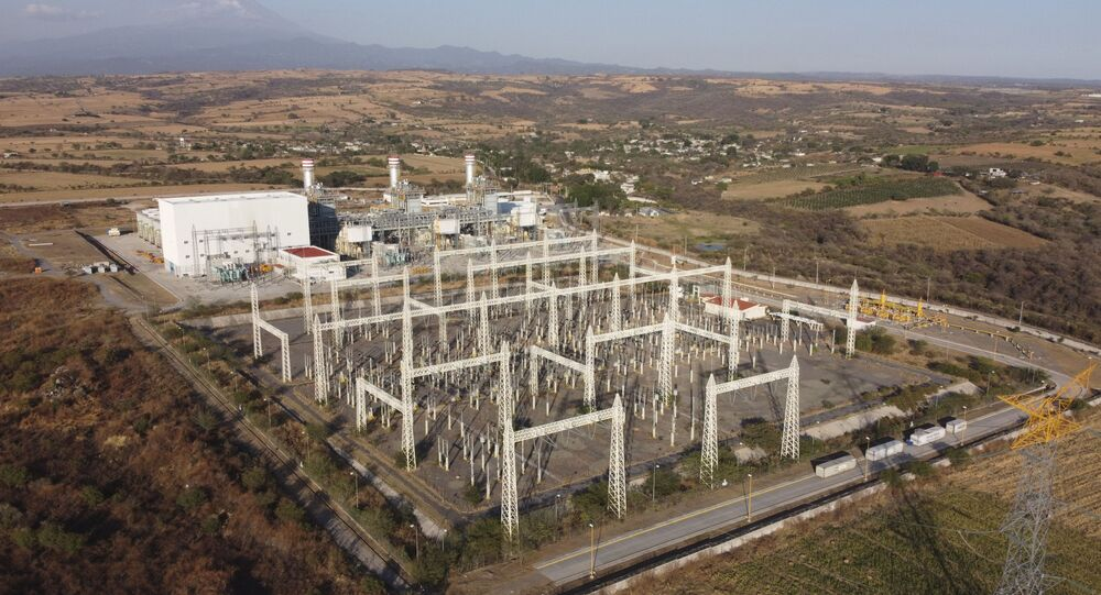 In this Feb. 22, 2020 file photo, a newly built power generation plant that is part of a mega-energy project including a natural gas pipeline traversing three states is seen with the Popocatepetl Volcano in the background near Huexca, Morelos state, Mexico.