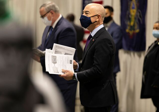 U.S. Homeland Security Secretary Alejandro Mayorkas hands informational pamphlets to essential and public-facing workers arriving to receive their coronavirus disease (COVID-19) vaccine at one of FEMA's Community Vaccination Center in Philadelphia, Pennsylvania, U.S., March 2, 2021.