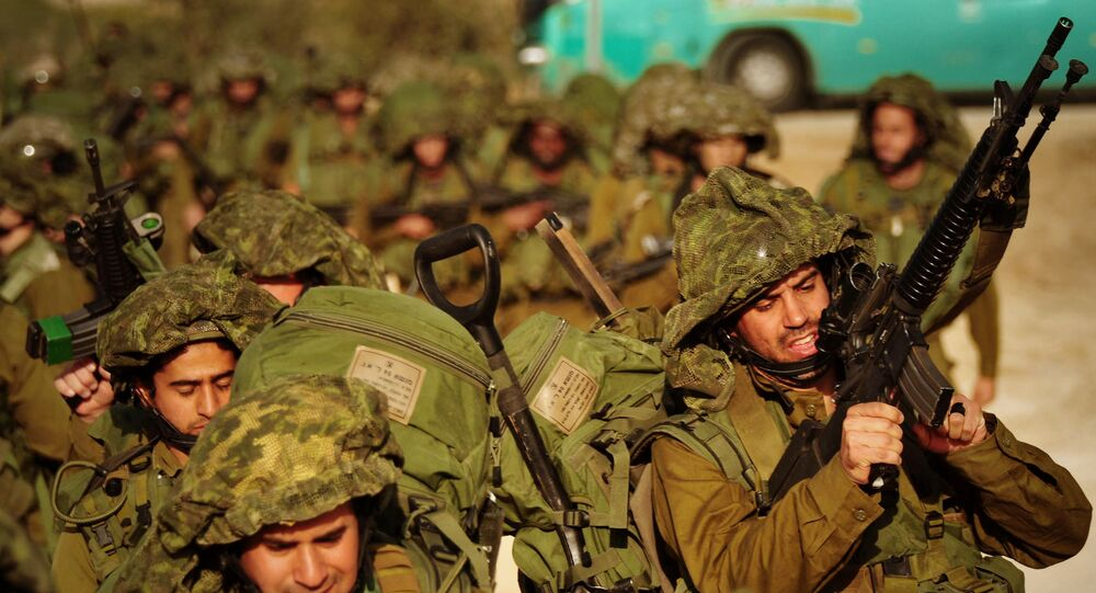 In this photo released by the Israeli army, Israeli soldiers walk towards the northern Gaza Strip as seen from the Israeli border with Gaza, Monday, Jan. 12, 2009.