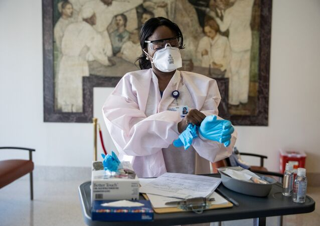 FILE PHOTO: FILE PHOTO: A nurse Kenia Georges wearing a protective mask puts on a glove during the coronavirus disease (COVID-19) pandemic, at NYC Health + Hospitals Harlem Hospital in the Manhattan borough of New York City, New York, U.S., February 25, 2021