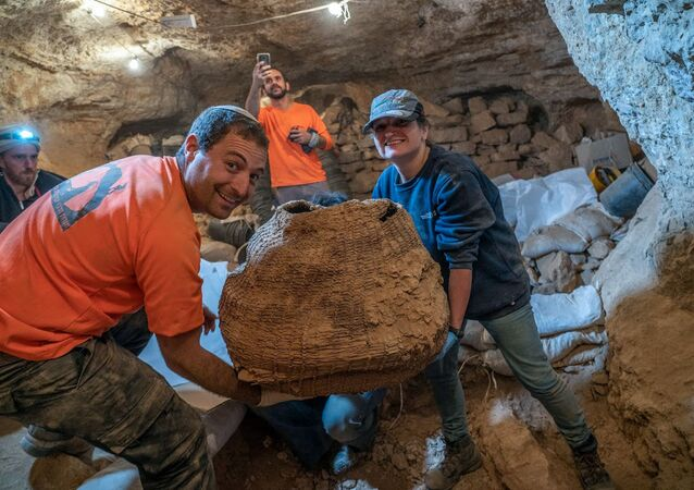 A handout picture provided by the Israeli Antiquities Authority shows archaeologists Haim Cohen (L) and Naama Sukenik transporting an ancient basket excavated from the Muraba'at cave in the Judean Desert near the Dead Sea.