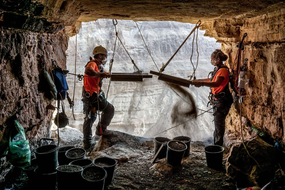 Archaeologists sifting soil during excavation in the Cave of Horror in the Judean Desert in Israel.