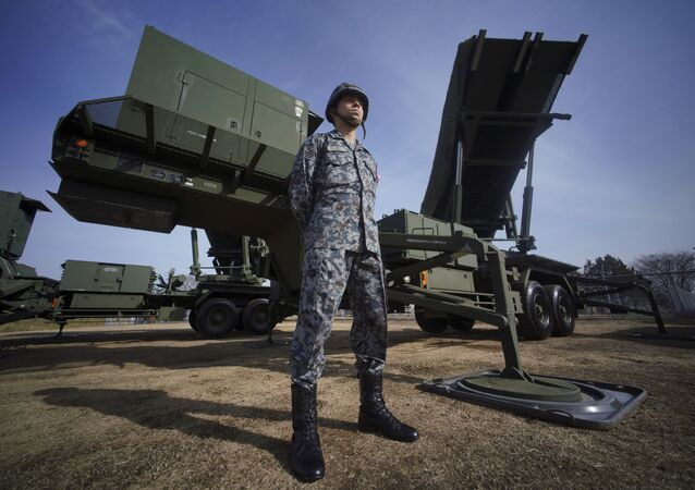 A member of Japan Ground Self-Defense Force stands guard next to a surface-to-air Patriot Advanced Capability-3 (PAC-3) missile interceptor launcher vehicle
