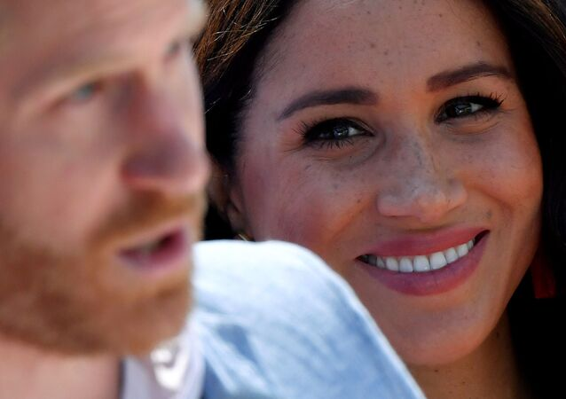 FILE PHOTO: Britain's Meghan, Duchess of Sussex, looks on as Prince Harry, Duke of Sussex, gives a speech, during a visit to the Youth Employment Services (YES) Hub in Tembisa township, near Johannesburg, South Africa, October 2, 2019